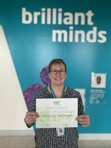 Dr Nicole Van Bergen holds her certificate for Excellence in Mitochondrial Research
