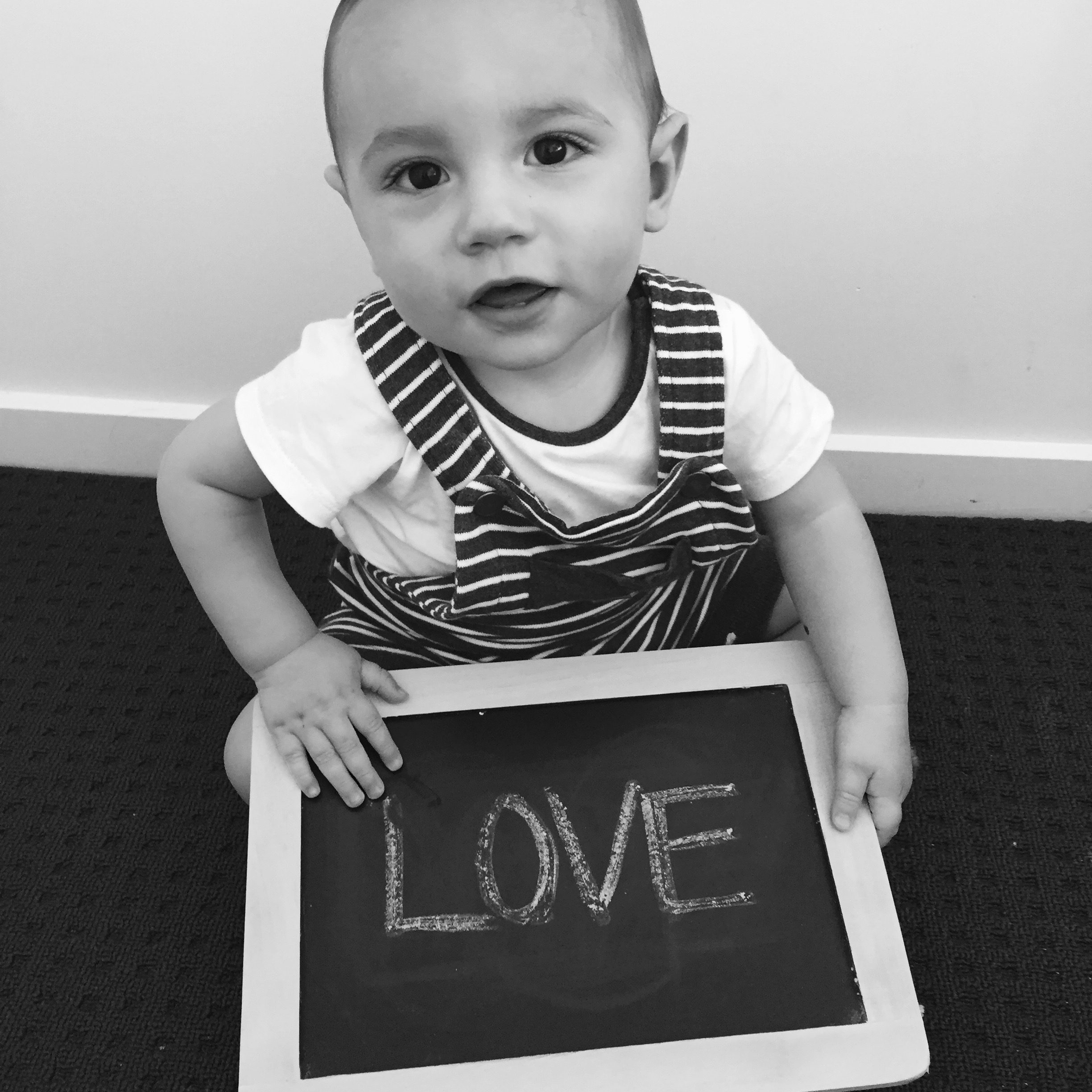 Child holding up a chalkboard with love written on it